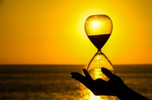 37386686 - time concept hourglass and sun setting on the atlantic ocean