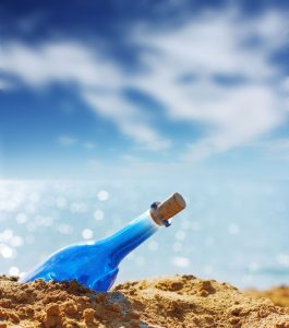 5751014 - blue glass bottle in sand and airy clouds like genie